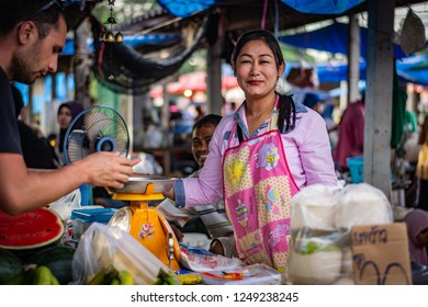 KOH LANTA, THAILAND - NOVEMBER 2018: Young woman sells fruit at a market on the island of Koh Lanta, a woman accepts payment from a man, between them stands a weight, Thailand