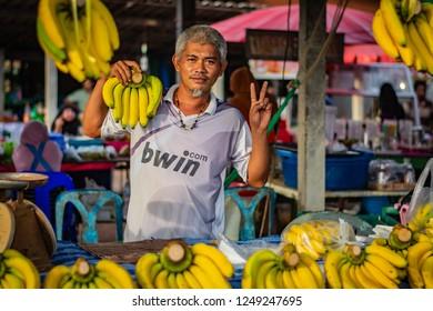 KOH LANTA, THAILAND - NOVEMBER 2018: The banana seller presents his goods at the market on the island of Koh Lanta in Thailand