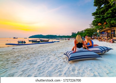 Koh Lipe, Thailand - 13.11.2019: Tourist are sitting on big pillows at Ko Lipe restaurant. Beach relaxation on pillows with summer drinks. Sunset in background. Romantic time at vacation. Paradise.