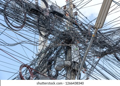 KOH PHANGAN, THAILAND - DECEMBER 22, 2018 : Chaos of cables and wires on an electric pole. Many electrical cable - wire and telephone line on electricity post, Thailand. Wire and cable clutter