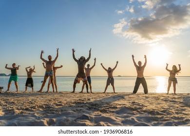 Koh Phangan, Thailand - feb 18, 2019 : Young peope dancing at tropical beach near sea water at paradise island at sunset. Summer concept. Holiday travel.