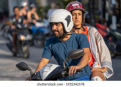 Koh Phangan, Thailand - february 08, 2020 : European man and girl riding a motorcycle on road at tropical island Koh Phangan, Thailand