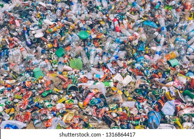 Koh Phangan, Thailand - February 19, 2019: PLASTIC POLLUTION in the jungle. Dirty plastic bottles and bags on a garbage. Ocean pollution, plastic in water. Pollution and recycle eco concept.