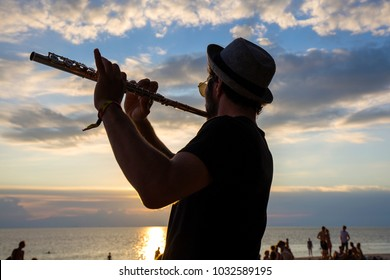 KOH PHANGAN, THAILAND - JANUARY 14, 2017: An unidentified musician man play the flute at sunset on the beach during a full moon party in island Koh Phangan, Thailand