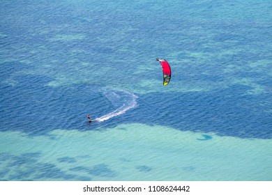 KOH PHANGAN, THAILAND - MARCH 02, 2018 : Young man kitesurfing in ocean, extreme summer sport on the island Koh Phangan, Thailand