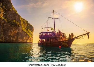 Koh Phi Phi Lee, Thailand - April 3, 2018 : A big boat in pirate style with many tourists enjoy a sunset at Maya Bay on Phi Phi island.