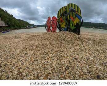 Koh Phi Phi Leh / Krabi province / Thailand - November 2017: Summer shoes, beach sandals, Havaianas in the sand of Loh Dalum Beach, Koh Phi Phi Don, Thailand.