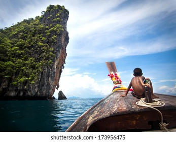 Koh Phi Phi, Thailand - May 09: Boy on traditional Thai long tail boat on the way to famous Maya Bay, Ko Phi Phi Island, Thailand.