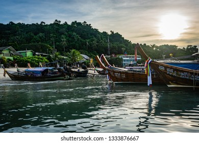 KOH PHI PHI, THAILAND - NOVEMBER 2018: Boats lined up at the edge of the island at dawn, morning sun in the sky, green trees and palm trees in the background, beach houses close to the sea