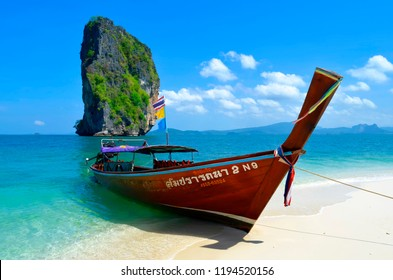 Koh Poda, Thailand - April 27, 2015: Long tail boat mooring at the beach with the famous Ko Ma Tang Ming rock in the background, in the Ao Nang bay.