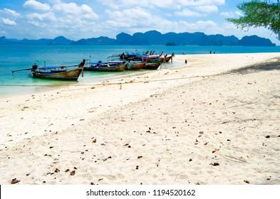 Koh Poda, Thailand - April 27, 2015: Long tail boats mooring at Koh Poda with Railay Beach and Phra Nang Beach in the background, in the Ao Nang bay.