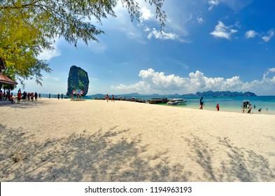 Koh Poda, Thailand - April 27, 2015: Long tail boats mooring at the beach with the Ko Ma Tang Ming rock and the Ao Nang bay in the background.