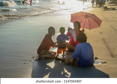 KOH SAMET, THAILAND - DEC 9, 2006:  family relaxes at the beach in Koh Samet in sunset. equipped with umbrella for sun protection they sit togethter at the beach. They symbolize family life.