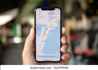 Koh Samui, Thailand - April 15, 2018: Man hands holding iPhone X with application cartographical service Apple Maps in the screen. iPhone 10 was created and developed by the Apple inc.