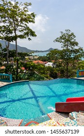 Koh Samui, Thailand - April 19, 2019:   Tropical infinity swimming pool surrounded by green forest on Koh Samui island in Thailand