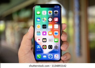 Koh Samui, Thailand - April 9, 2018: Man hand holding iPhone X with IOS 11 on the screen. iPhone 10 was created and developed by the Apple inc.