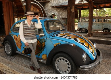 KOH SAMUI, THAILAND - FEBRUARY 7, 2014: Legengary retro car Volkswagen Beetle, blue vintage automobile on Koh Samui island (Thailand) and girl dressed in british style with hat