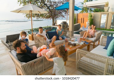 KOH SAMUI, THAILAND - JANUARY 21; modern young families sitting around outside enjoying one and others company in warm tropical late sun in beachside environment January 21, 2018 Koh Samui Thailand
