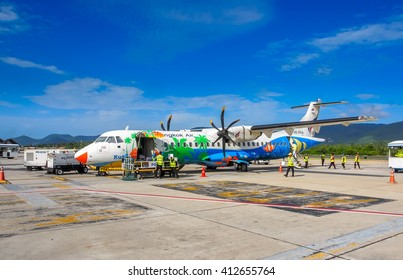 KOH SAMUI, THAILAND - July 11, 2014: Bangkok Airways's ATR-72 propeller aircraft is landed in Koh Samui, Thailand and unloads passenger's luggage. The aircraft is decorated in beach holiday theme.
