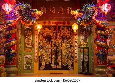 Koh Samui, Thailand - March 1, 2019: Entrance to the chinese temple guardered by dragons on pillars and samurais on doors at night