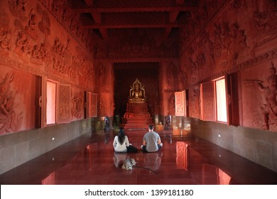 KOH SAMUI, THAILAND - MARCH 10, 2019: Wat Sila Ngu (Red Temple) on Koh Samui island (Thailand), indoor, and praying people. Buddhist religious architecture