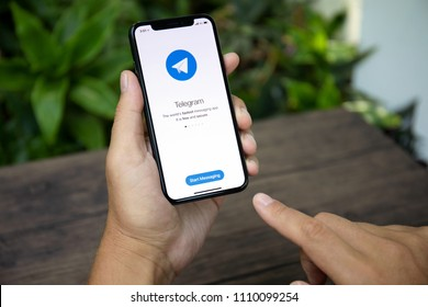 Koh Samui, Thailand - March 26, 2018: Man hand holding iPhone X with social networking service Telegram on the screen. iPhone 10 was created and developed by the Apple inc.
