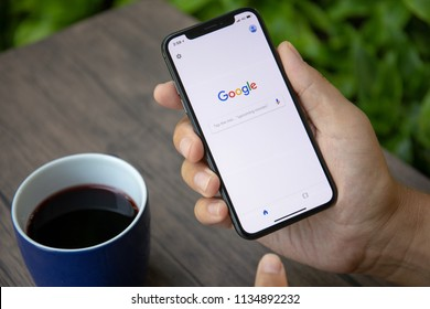 Koh Samui, Thailand - March 26, 2018: Man holding iPhone X with social networking service Google on the screen. iPhone was created and developed by the Apple inc.