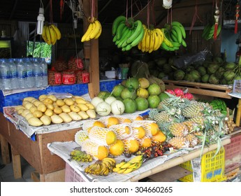 KOH SAMUI, THAILAND - OCTOBER 24, 2013: Fruit shop with pile of pineapple,banana,papaya,coconut,mango,tamarind   and water bottles