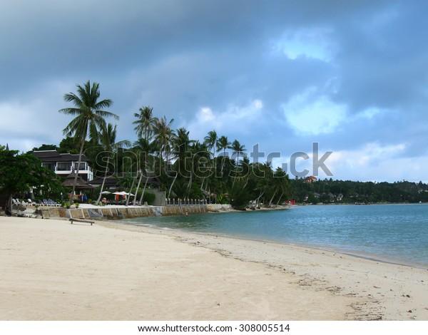 KOH SAMUI, THAILAND - OCTOBER 24, 2013: Lamai beach in rain season, dark blue cloudy sky,  resort, palm trees, white sand