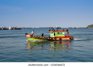 Koh Sichang, Thailand - January 30, 2018: The small coastal fishing boat with  4 fishermen on the boat entering Koh Sichang or Sichang island port.
