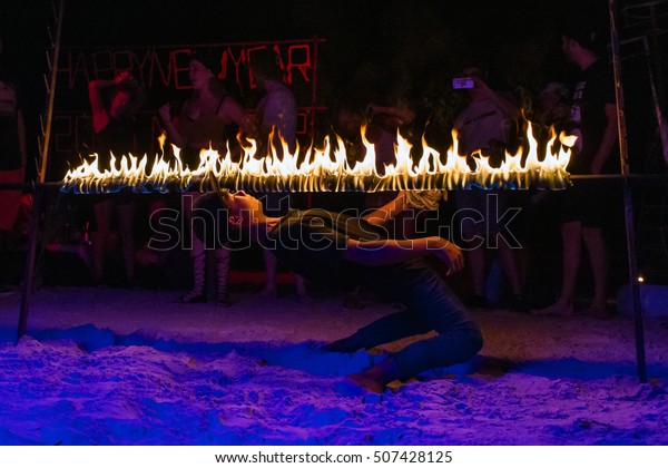 KOH TAO, THAILAND - DECEMBER 25, 2015: A Thai man limbos under a bar of fire during a Christmas party in Koh Tao island, Thailand