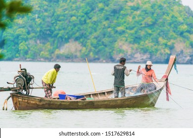 Koh Tao, Thailand - March 25, 2018: Three men in a boat are fishing on the net.