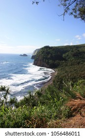 The Kohala Coastline at Pololu Valley, lush vegetation covering the Kohala Mountains, black sand beach and white foaming Pacific Ocean waters coming ashore