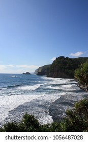 The Kohala Coastline at Pololu Valley, lush vegetation covering the Kohala Mountains and white foaming Pacific Ocean waters coming ashore