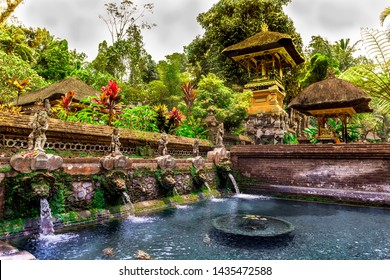 Koi pond with clear holy spring water at Gunung kawi Sebatu Temple with stone sculpture fountains, a pagoda with a shrine of offerings to the gods and tropical & exotic plants in Bali, Indonesia, Asia