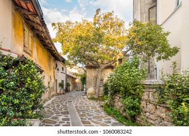 Kojsko, Slovenia - 8.September, 2017: A small narrow street in the castle Kojsko painted with golden sun rays, Municipality Brda, Goriza, Slovenia