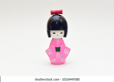 Kokeshi Japanese national doll in a pink kimono  wooden doll on isolated white background