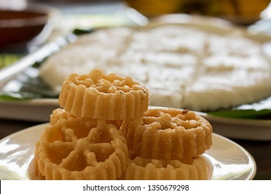 Kokis on a plate with a plate of blurred milk rice in the background - Side View A Sri Lankan Sinhala and Tamil New Year Festive Food. Also known as Sinhala and Tamil Avurudhu/Avurudu Sweets