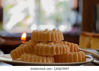 Kokis on a plate with a lit oil lamp in the background - Side View A Sri Lankan Sinhala and Tamil New Year Festive Food. Also known as Sinhala and Tamil Avurudhu/Avurudu Sweets