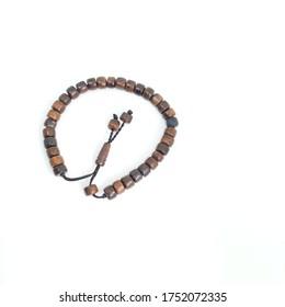 Kokka wood bracelets, muslim prayer beads on a white background. Flaf lay.