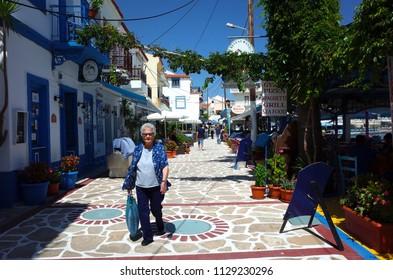 Kokkari, Samos island, Greece - 15 May, 2018: Old woman walking on colorful street with outdoor restaurants in Kokkari fishing village, Samos Island is popular tourist destination in Aegean Sea