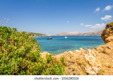 Kokkina Beach, Leros, Dodecanese Islands/ Greece – July 18 2017: Beautiful sunny coast view to the greek blue sea with crystal clear water beach with some boats fishing cruising surrounded by hills