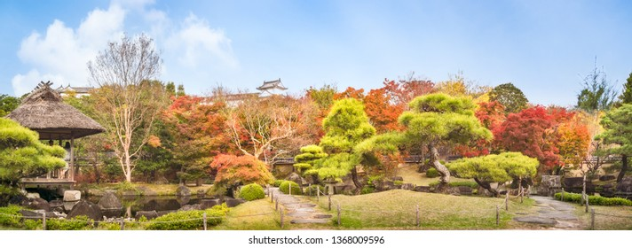 Koko-en Garden, Himeji, Japan -November 8, 2018: Chinese style garden panorama in autumn at Koko-en Japanese Gardens with small stone bridges over the creek and with the rooftop of Himeji Castle over