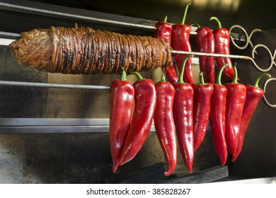Kokorec And Some Sweet Red Peppers On A Skewer. Kokorec is a traditional Turkish street food made of lamb intestine.