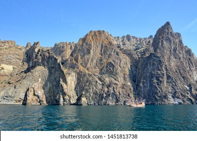 "KOKTEBEL, CRIMEA - View on the sailing yacht approaching  the picturesque cliff ""Golden Gate"", the main tourist attraction at the ancient volcanic rock formation of Kara Dag Mountain (""Black Mount"")."