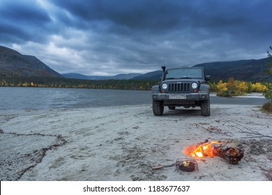 Kola peninsula. Murmansk region, Russia, September 10, 2018: black Jeep Wrangler Sahara on the shore of a mountain lake. Wrangler is a compact four wheel drive off road and sport utility vehicle