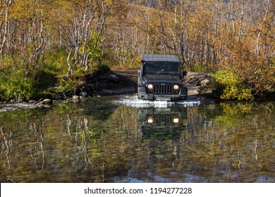 Kola peninsula. Murmansk region, Russia, September 8, 2018: black Jeep Wrangler Sahara moving a mountain river in the Murmansk region. Off road and sport utility vehicle