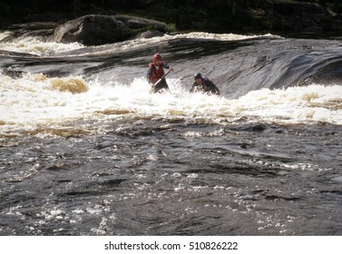 KOLA PENINSULA, RUSSIA - 17 AUGUST 2008: Men on an inflatable catamaran overcome the threshold of the turbulent river. Catamaran is not visible.