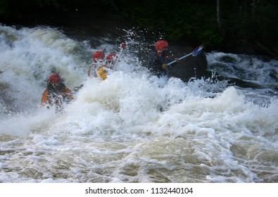 KOLA PENINSULA, RUSSIA - AUGUST 15 2008: Team of men on an inflatable catamaran at rough river