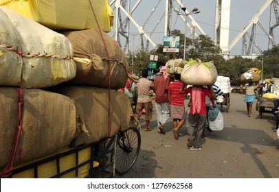 KOLAKATA, INDIA -DEC 04 : Unidentified people walk with heavy baggages on their heads in the background of Howrah bridge on December 04, 2018 in Kolkata, West Bengal,India.